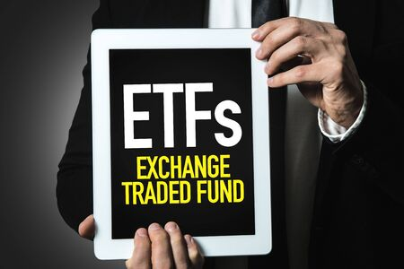 Person holding a tablet with ETFs Exchange Traded Fund Banco de Imagens