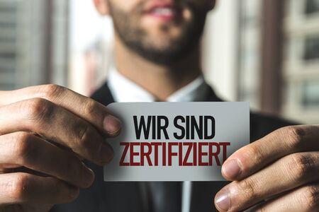 Person holding a card with Wir Sind Zertifiziert