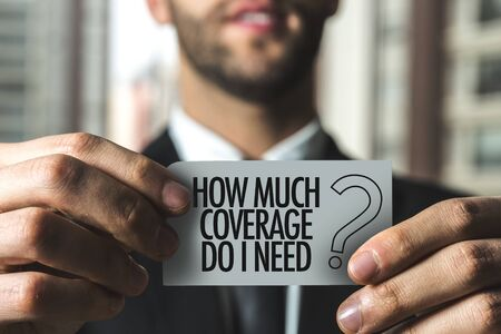 Person holding a card with How much coverage do I need 版權商用圖片