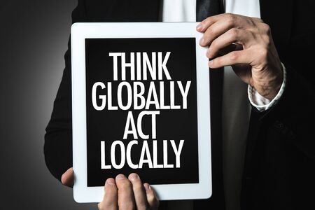 Person holding a tablet with Think Globally Act Locally