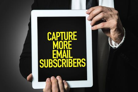 Person holding a tablet with Capture More Email Subscribers