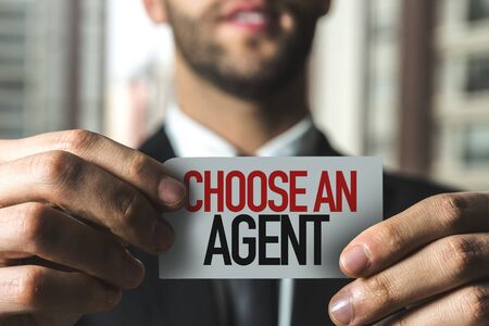 Businessman holding a card with the words Choose An Agent