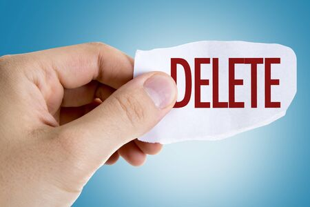 Person holding a piece of paper with the word Delete