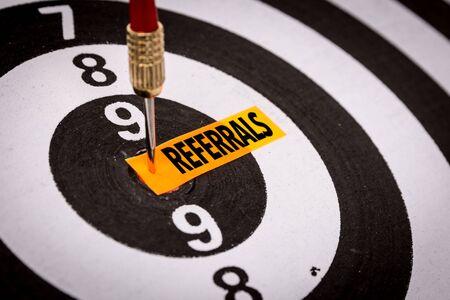 Referrals sticky note on dart board