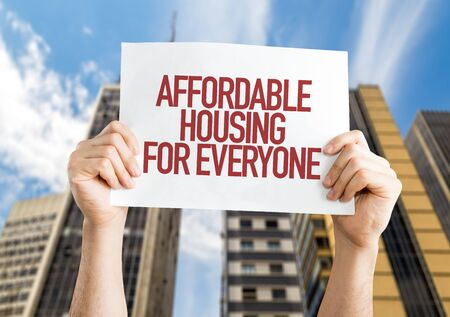 Person holding a placard with the words Affordable Housing For Everyone
