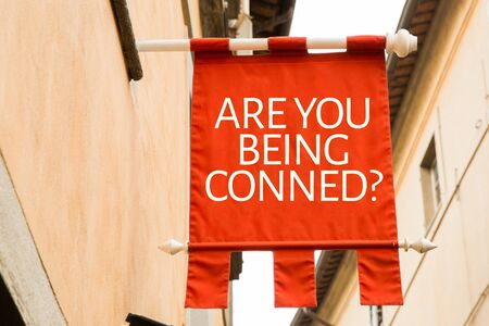 Are You Being Conned sign in a street