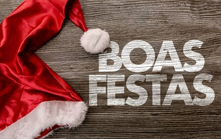 Santa hat with the words Boas Festas on wooden background Stockfoto