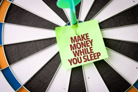 Dart with the words Make Money While You Sleep Archivio Fotografico