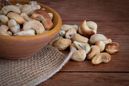 Tasty cashew nuts in bowl on wooden table. Space for text.
