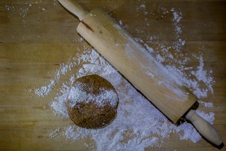 Balls of integral dough with rolling pin on wooden board