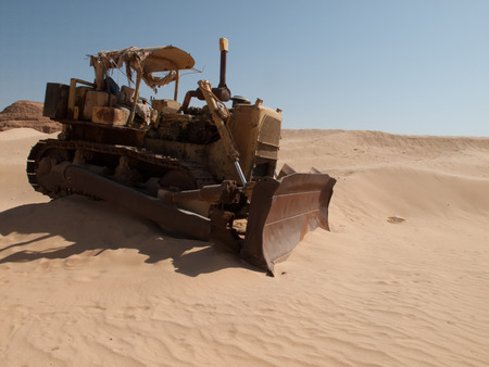 An old bulldozer abandoned in the middle of the desert in Saudi Arabia Stock Photo