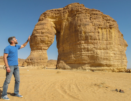 Funny picture with a man stroking the rock formation known as the Elephant Rock in Al Ula, Saudi Arabia (KSA) Stock Photo