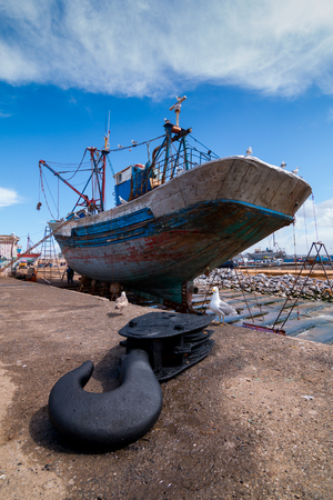 A fishing boat docked at the Essaouira port waits for a full repair with a boat hook in the foreground