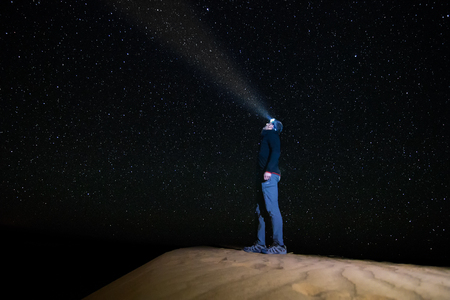 A standing man looking at the starry sky with a flashlight, on a dune in the desert of Erg Chebbi