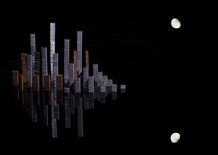 A simulated city skyline created with staples that form skyscrapers and the moon with a dark background and its reflection.