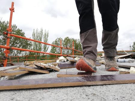 Un trabajador de la construcción tiene un accidente mientras camina por un sitio con escombros y pisa un clavo. Foto de archivo
