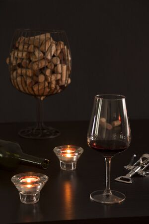 Glass of wine in the foreground with an empty bottle, a corkscrew and corks from the bottles inside a vase simulating a glass of wine in dark tones background Фото со стока