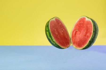 A watermelon cut in half on a blue and yellow background 免版税图像