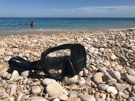 Close-up of a diving mask on the stones of a beach. Stock fotó