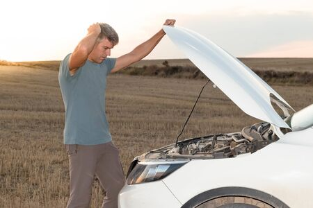A man in the middle of the field checking the engine of his broken down car at sunset. Lifestyle concept Stock Photo