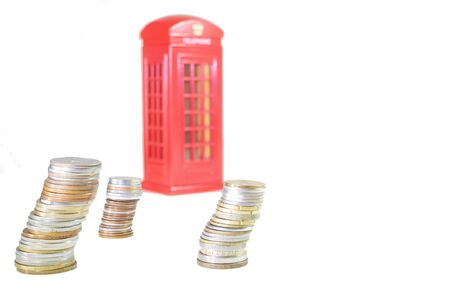 UK Brexit. piles of coins with an with a phone booth in the background out of focus on an overexposed white background. Brexit concept Stockfoto