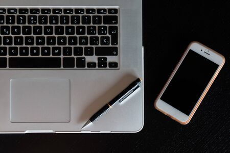 Partial view of a silver keyboard of a laptop with a smartphone and a pencil on a dark wood desk Stock Photo