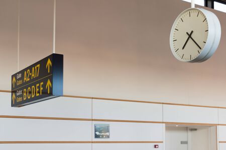 A panel indicating the boarding gates and a clock inside an airport terminal. Travel concept