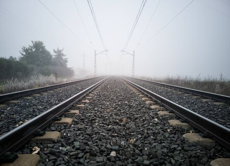 Train tracks and catenary posts disappear into thick fog in the country. Train concept