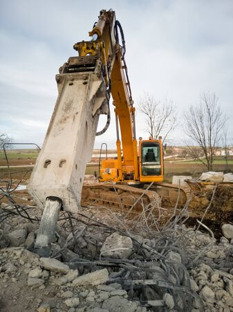 Close-up of a hydraulic breaker of a yellow excavator working on a demolition of reinforced concrete. Construction site