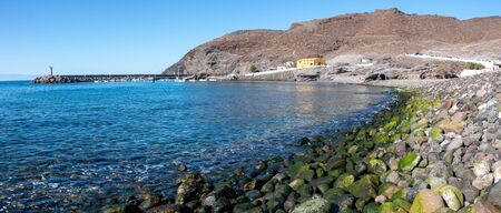 Panoramic view of Puerto de la Aldea with its pebble beach with moss in the foreground, on the island of Gran Canaria, Spain. Travel concept Foto de archivo