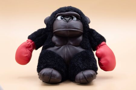 Stuffed toy gorilla boxer with angry face posing on a pale yellow background. Boxing concept