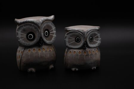Figure of a pair of wooden owls one bigger than another on black background. Couple concept