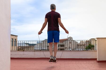 Man working out with a skipping rope on the terrace of his house. Sport in quarantine confinement