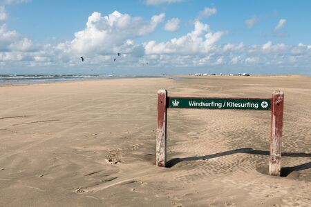 Sign indicating the windsurfing and kitesurfing area on a beach on the island of Romo, Denmark with people surfing in the background. Water sport concept