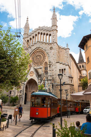 Soller, Spain - August 4, 2020: Old wooden tram the main square in front of the church in the town of Soller, Mallorca, Spain. Travel concept Editorial