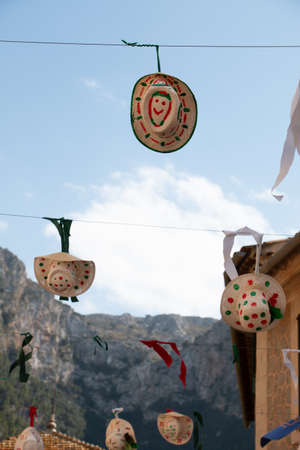 Funny decorated hats hanging from a thread on the street in a village festivals with mountains in the background. Celebration concept