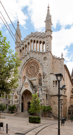 Facade of the church of San Bartolomé in Soller, in Majorca with the tracks of its famous tram in front of it. Culture travel concept Imagens