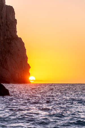 The sun setting behind a cliff above the horizon line of the sea with a golden sky. Vacations concept