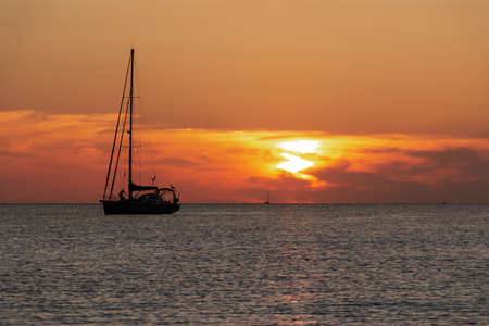 Seascape of silhouette of a sailing ship in the ocean at sunset. Vacation concept