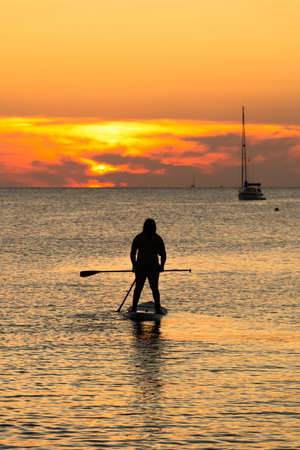 Rear view of two people silhouette on the same board of paddle surf at sunset with a sailboat in background. Holiday concept