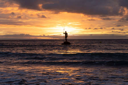Statue of the God Neptune with the sun just behind it on the beach of Melenara on the island of Gran Canaria (Spain) at sunrise. Travel concept Standard-Bild