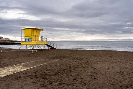 A yellow lifeguard tower on a beach on the island of Gran Canaria (Spain) at sunrise with cloudy sky. Beach concept Standard-Bild