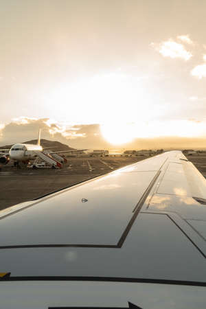 Wing of a plane in the foreground on the runway with a plane in the background ready to board at sunset. Travel concept