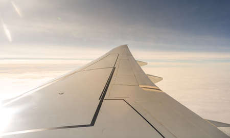 Wing of an airplane in foreground flying above sea of clouds. Travel concept