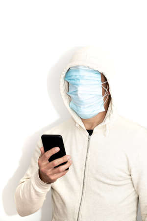 Unrecognizable hooded man with his face covered in protective masks wearing white jacket looking at his phone and white background. Standard-Bild