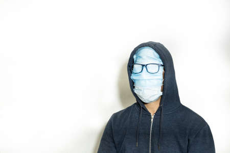 Portrait of a man with his face covered in masks and glasses above them with a blue jacket with hood on a white background
