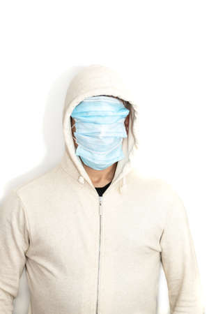 Vertical portrait of hooded man with his face covered in protective masks with white jacket and white background