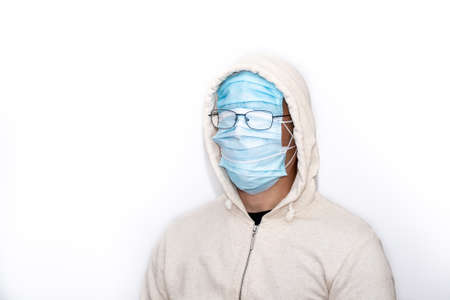 Portrait of a man with his face covered in masks and glasses above them with a white jacket with hood on a white background