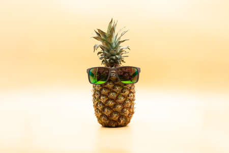 Funny pineapple with sunglasses over pastel yellow background. Summertime concept
