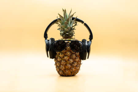Funny pineapple in sunglasses wearing wireless headphones looking at camera over pastel yellow background. Party concept